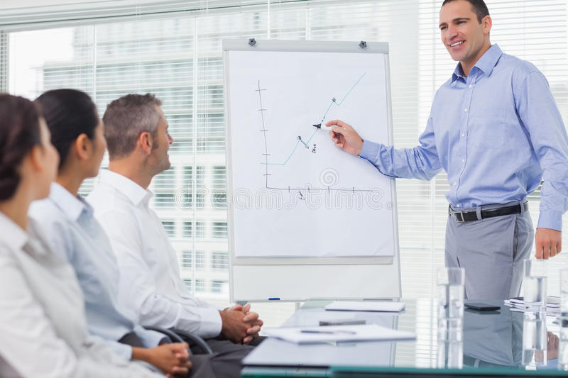Businessman analyzing graph during presentation. In bright office stock photos