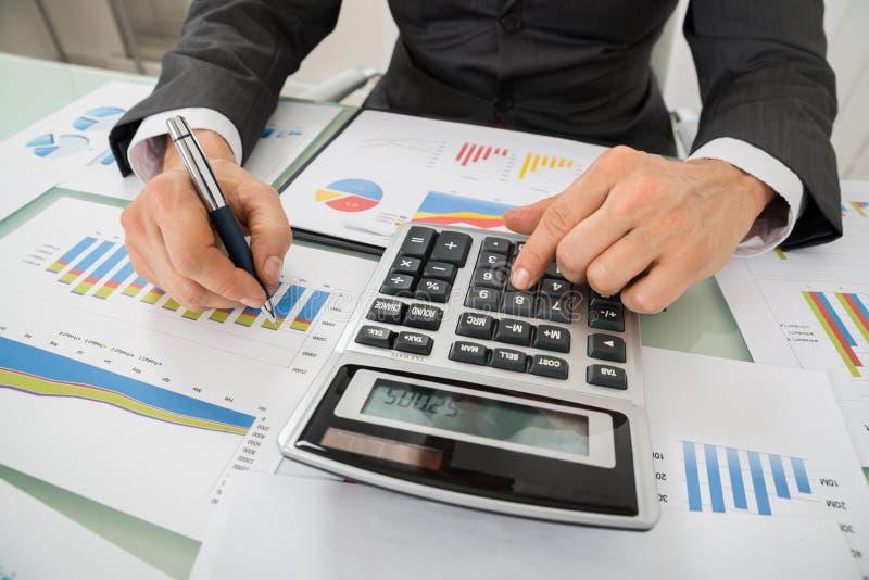 Businessman Analyzing Graph And Using Calculator stock photo