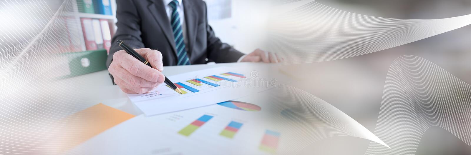 Businessman analyzing graphs; panoramic banner. Businessman analyzing graphs at office; panoramic banner royalty free stock photography