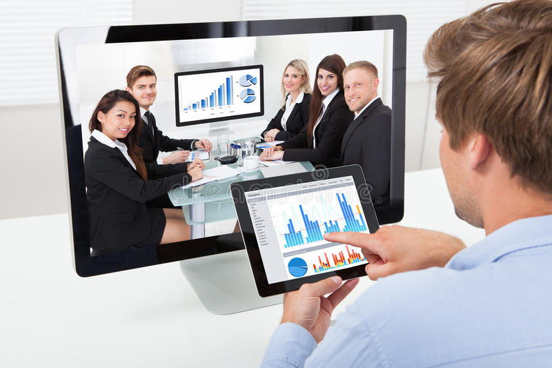 Businessman analyzing graphs while video conferencing royalty free stock image