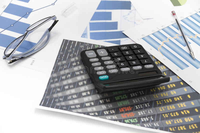 Businessman analyzing investment charts with calculator and laptop. Photo of the Businessman analyzing investment charts with calculator and laptop stock image