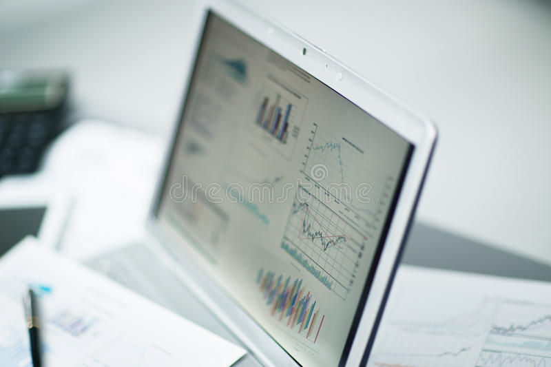Businessman analyzing investment charts with laptop royalty free stock image