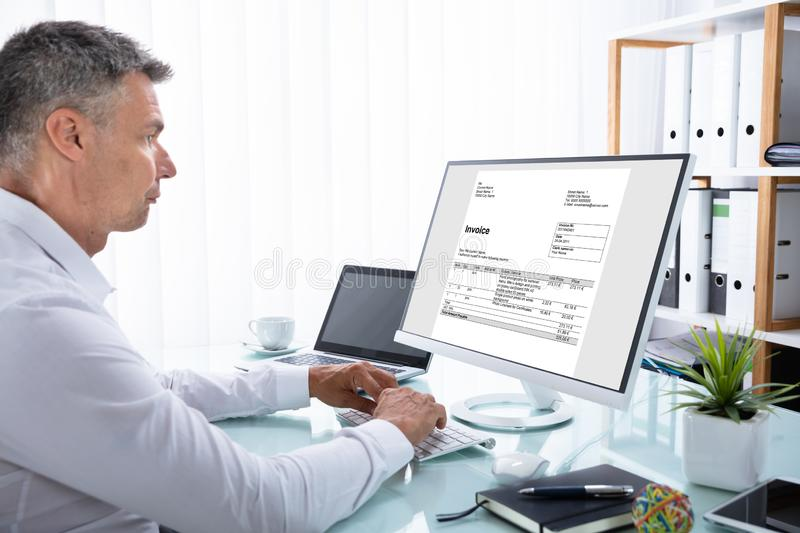 Businessman Analyzing Invoice On Computer. Side View Of A Mature Businessman Analyzing Invoice On Computer stock photography