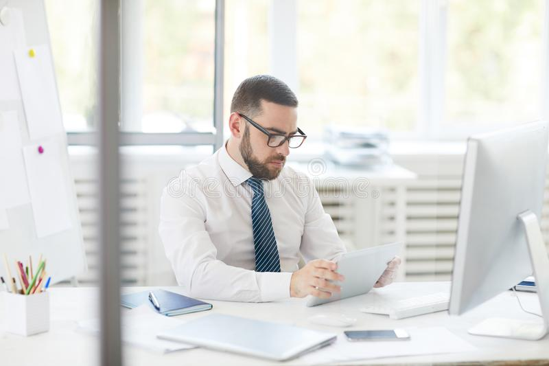 Businessman analyzing online chart. Concentrated young bearded businessman in glasses sitting at desk and analyzing online chart on tablet royalty free stock photo