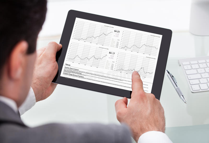 Businessman Analyzing Stock Market Status On Digital Tablet royalty free stock image