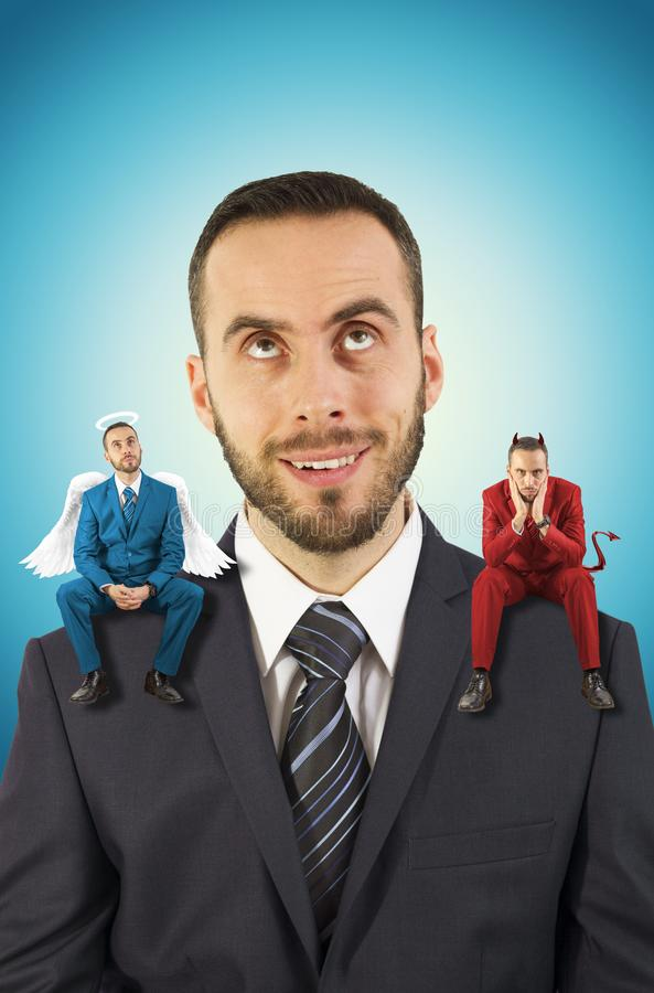 Businessman with angel and devil on his shoulders. Young and handsome businnessman in a black suit getting advice from angel and devil on his shoulder royalty free stock images
