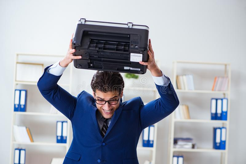 The businessman angry at copying machine jamming papers. Businessman angry at copying machine jamming papers stock photo
