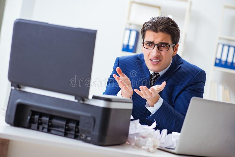 The businessman angry at copying machine jamming papers. Businessman angry at copying machine jamming papers stock photography