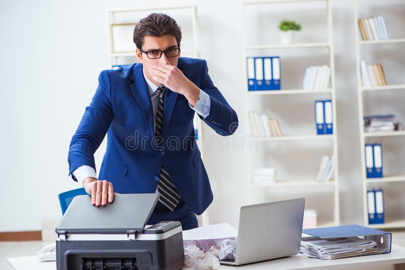 The businessman angry at copying machine jamming papers. Businessman angry at copying machine jamming papers royalty free stock images