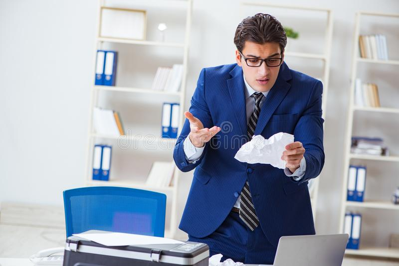 The businessman angry at copying machine jamming papers. Businessman angry at copying machine jamming papers stock image
