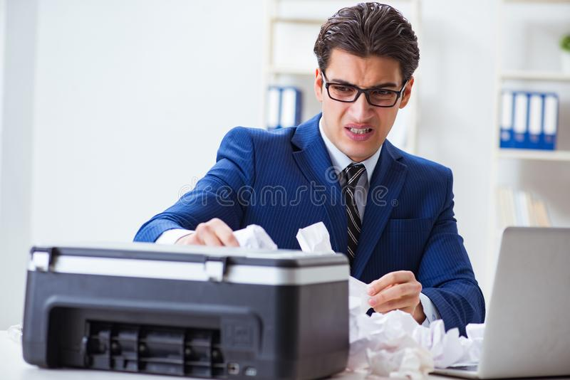 The businessman angry at copying machine jamming papers. Businessman angry at copying machine jamming papers royalty free stock photo