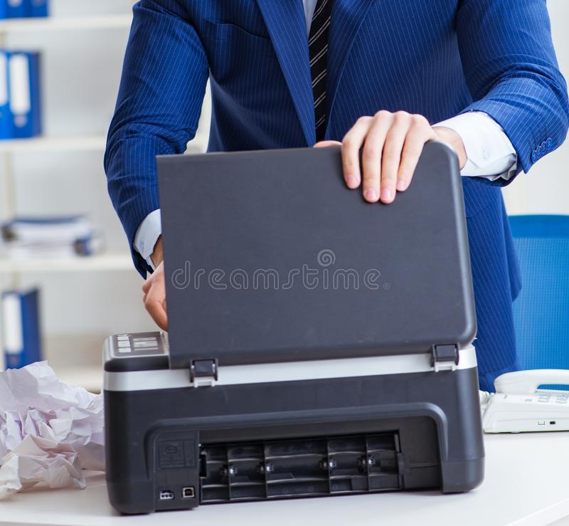 Businessman angry at copying machine jamming papers. The businessman angry at copying machine jamming papers stock photography