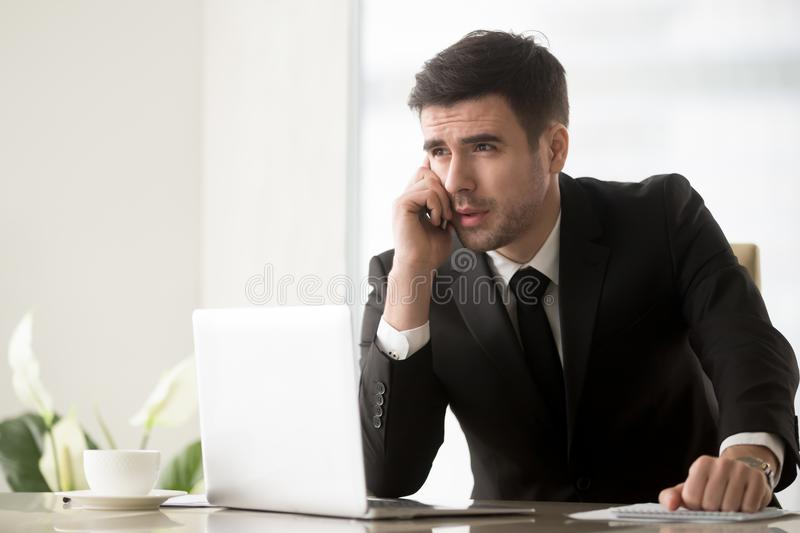 Businessman answering phone call at desk in office stock images