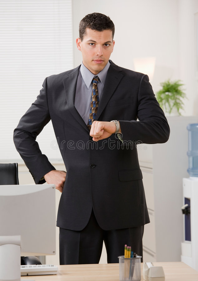 Businessman anxiously checking wristwatch stock images