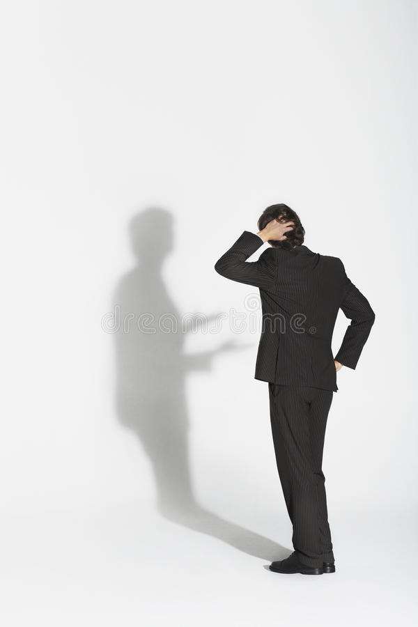 Businessman Arguing With Own Shadow. Full length rear view of a young businessman arguing with own shadow against white background stock photo