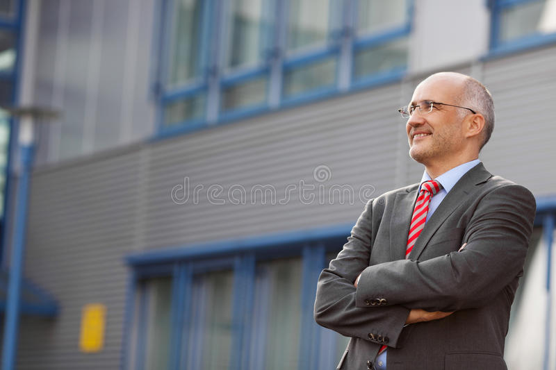 Businessman With Arms Crossed Standing Against Office royalty free stock images