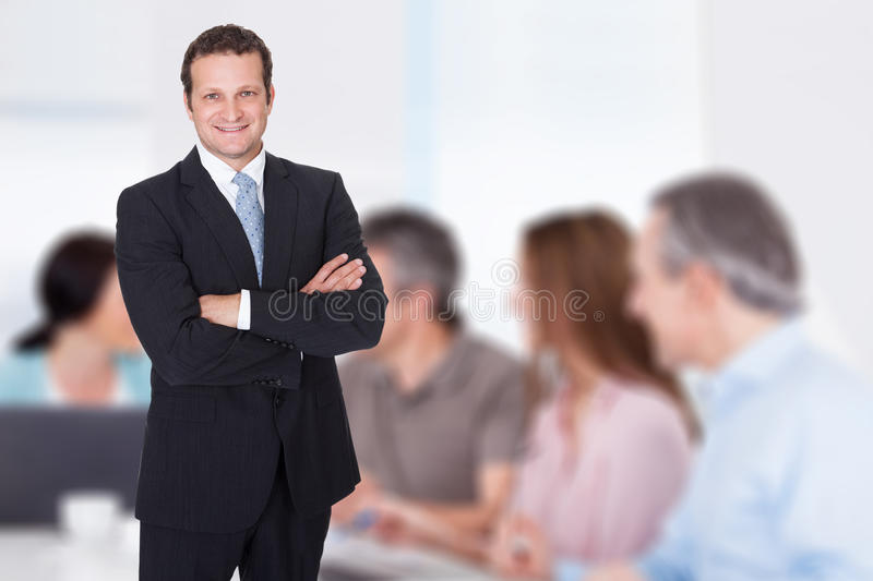 Businessman with arms crossed standing in boardroom royalty free stock photos