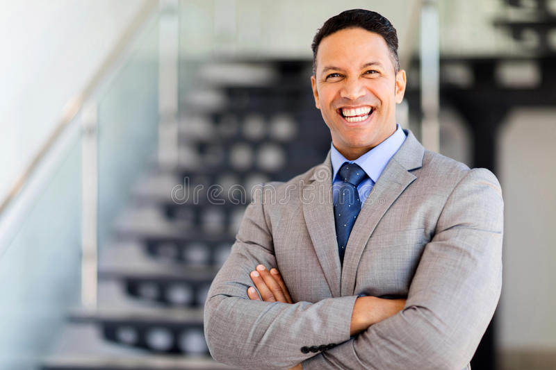 Businessman with arms folded. Cheerful businessman with arms folded in modern office royalty free stock images