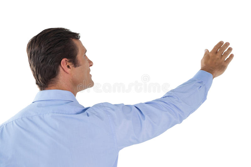 Businessman with arms raised touching invisible interface royalty free stock photos