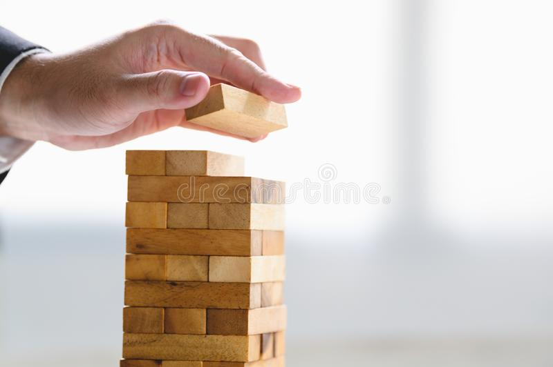 Businessman arranging wood block and stacking as tower by hand. Business organization and company growth progress. Success of stock photo