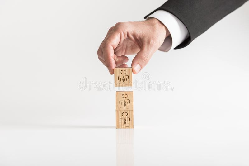 Businessman arranging wooden blocks with human icons. Customer-managed relationship Concept against white background royalty free stock photos