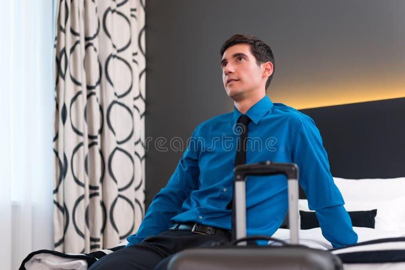 Man arriving in hotel room. Businessman at arrival in room of design hotel royalty free stock image