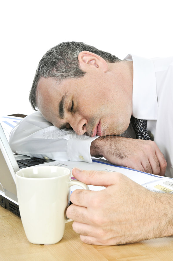 Businessman asleep at his desk on white background royalty free stock photo