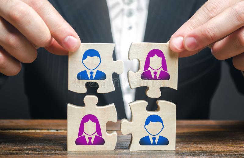 Businessman assembles a team in the form of a set of puzzles. Search, hiring and recruitment staff. Creating an efficient. And productive business unit royalty free stock photo