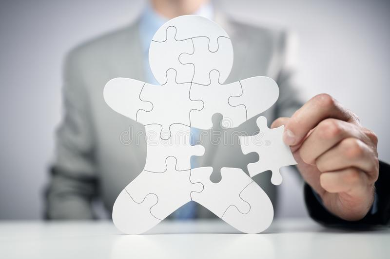 Businessman assembling jigsaw puzzle human team employee. Concept royalty free stock photography