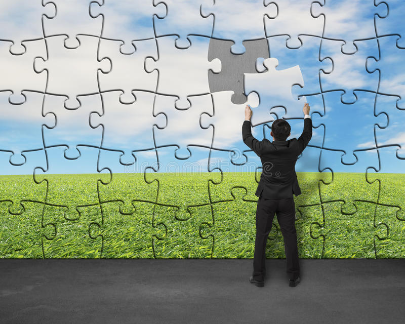 Businessman assembling last missing puzzle on wall. For landscape royalty free stock images