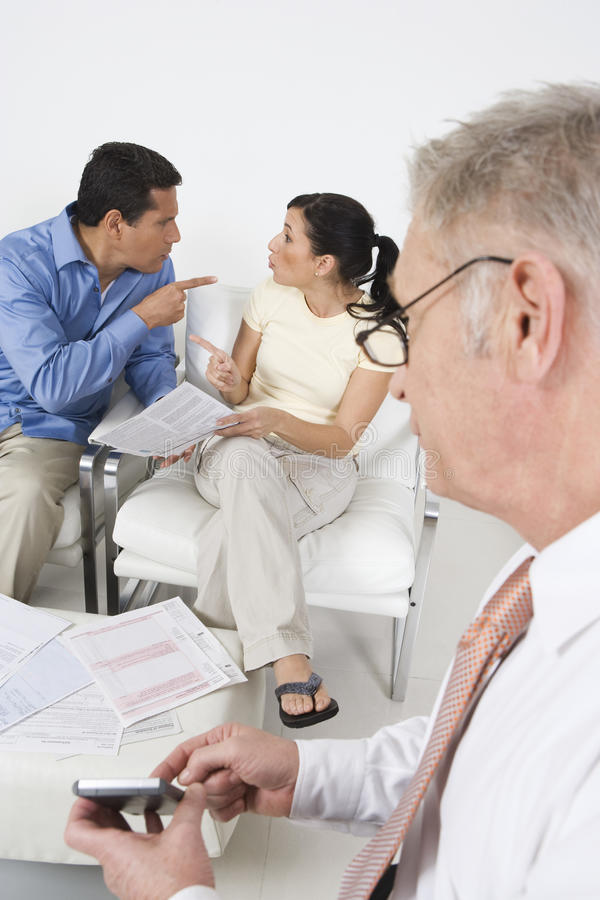 Businessman Assisting Angry Couple Royalty Free Stock Images
