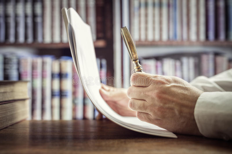 Businessman or attorney with magnifying glass reading documents stock photography