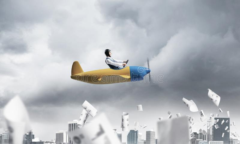 Businessman in aviator hat driving paper plane. Crisis management and control in difficult situation concept. Businessman in aviator hat driving propeller plane stock images