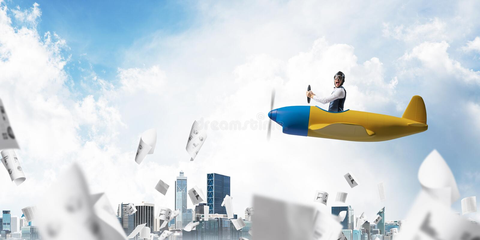 Businessman in aviator hat driving plane. Businessman in aviator hat and goggles driving propeller plane above cityscape. Papers falling down on background of stock images