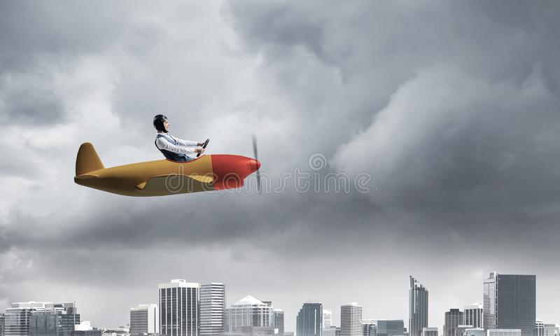 Businessman in aviator hat and goggles. Driving propeller plane in storm. Side view of pilot in small airplane. Megalopolis panorama with dramatic dark cloudy royalty free stock images