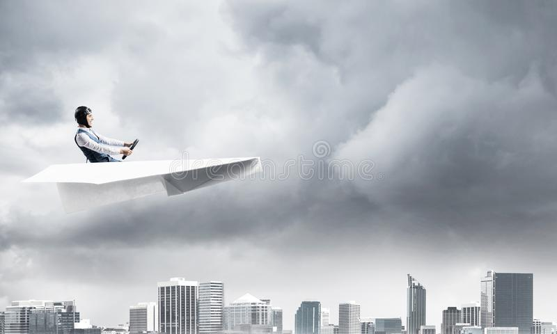 Businessman in aviator hat and goggles. Driving paper plane in storm. Crisis management concept. Side view of pilot in small paper airplane. Megalopolis stock photo