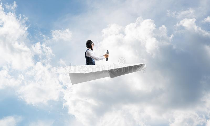 Businessman in aviator hat sitting in paper plane. And holding steering wheel. Pilot driving paper plane in cloudy blue sky. Extreme aviation hobby. Sky stock photos