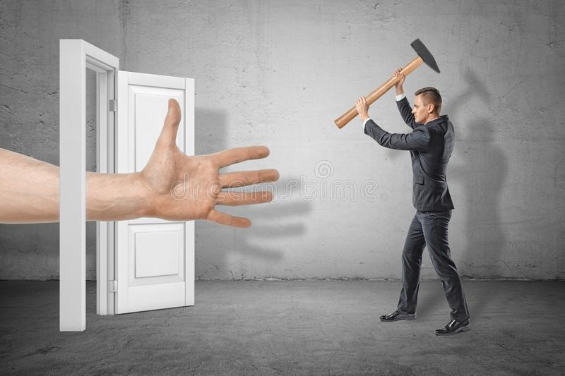 Businessman with axe in hands on the right ready to hit huge human hand reaching out through white doorway on the left. Defend your business interests. Violent stock photography