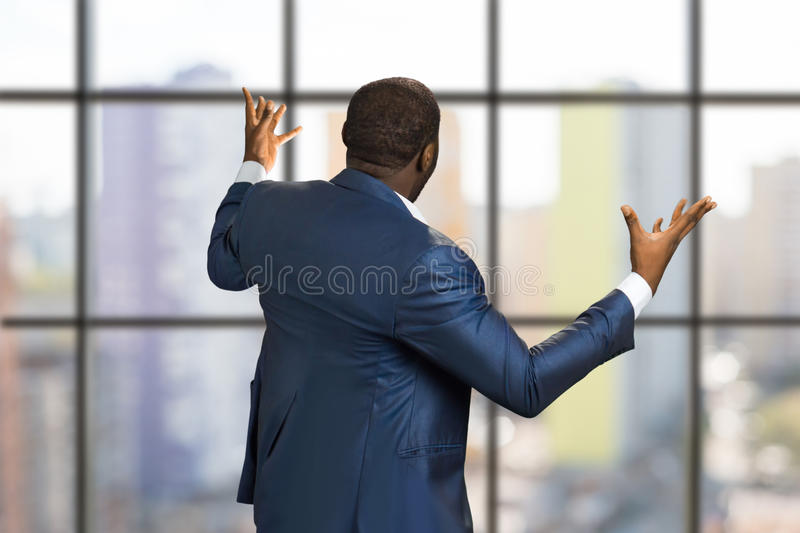 Businessman from back raising hands. stock image