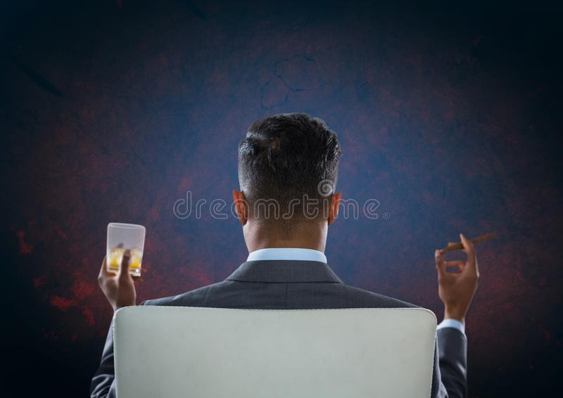 Businessman Back Sitting in Chair with drink glass and dark background. Digital composite of Businessman Back Sitting in Chair with drink glass and dark royalty free stock images