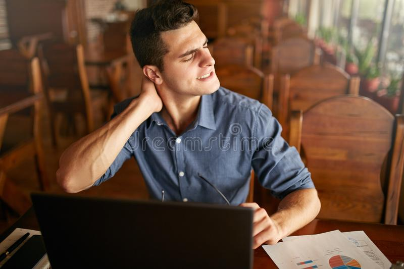 Businessman with backpain after long hours at work rubbing his neck because of ache. Overworked handsome freelancer man. With scoliosis working with laptop stock images
