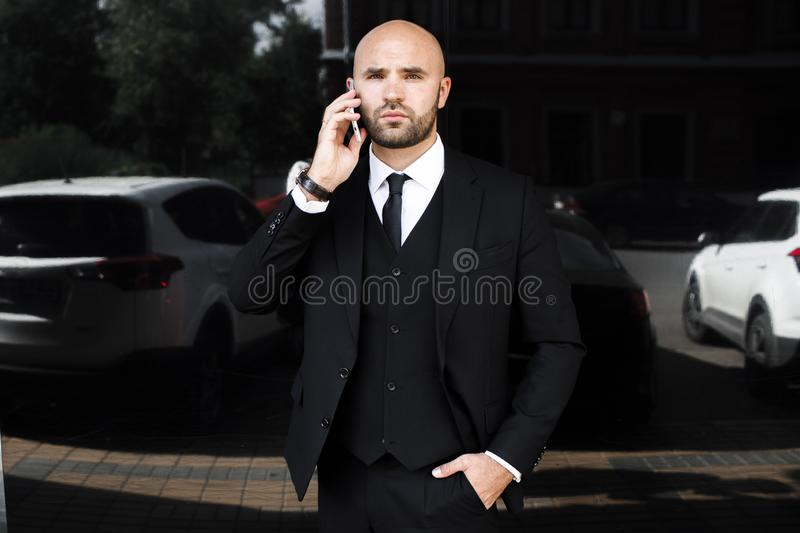 Businessman with a bag near the office talking on the phone royalty free stock photo