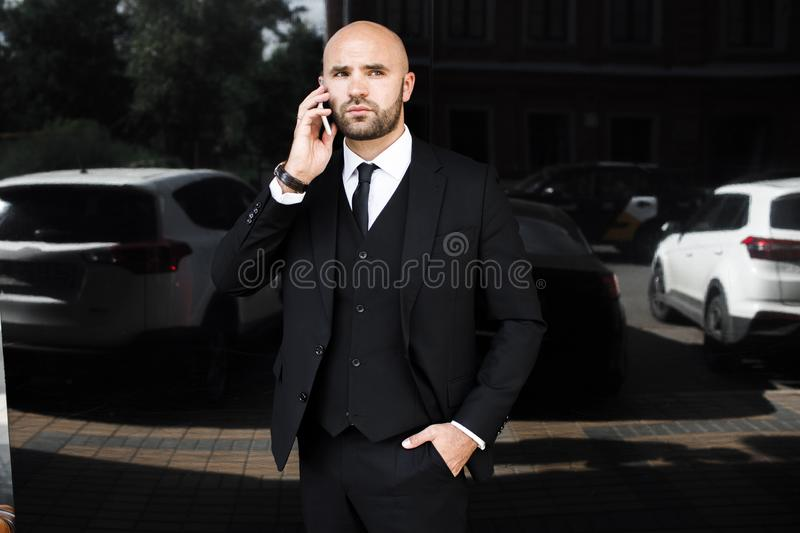 Businessman near the office talking on the phone stock photography
