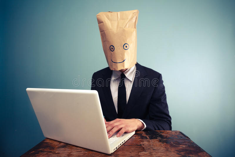 Businessman with bag over head working on computer royalty free stock image