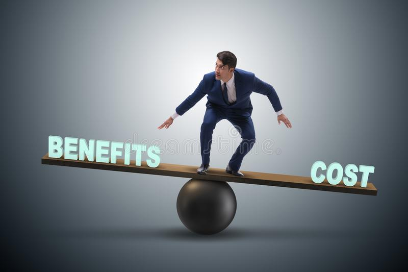 Businessman balancing between cost and benefit in business conce. Pt stock photo