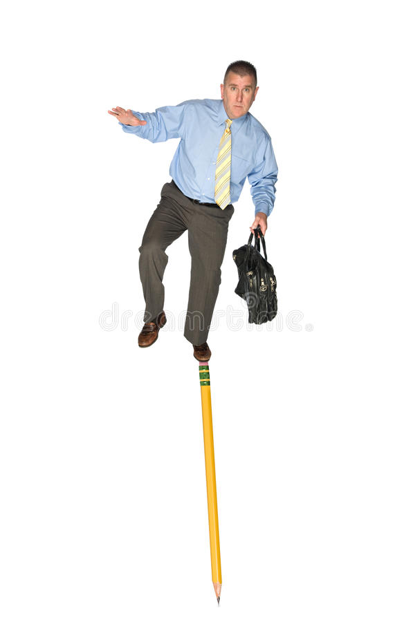Businessman balancing on pencil. A businessman carrying a briefcase balances himself on the eraser of a pencil. Good for skill, challenge or adversity business royalty free stock photo