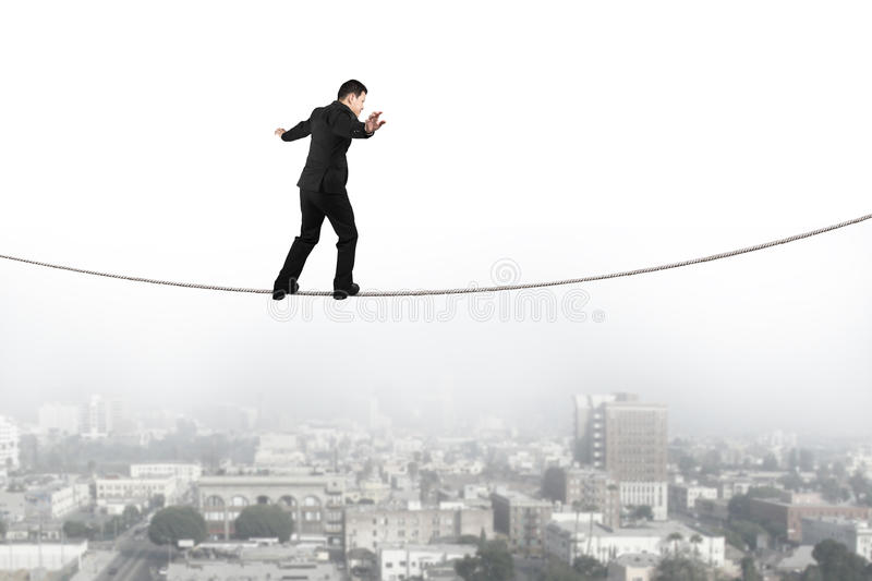 Businessman balancing and walking on the rope with urban scene stock photo