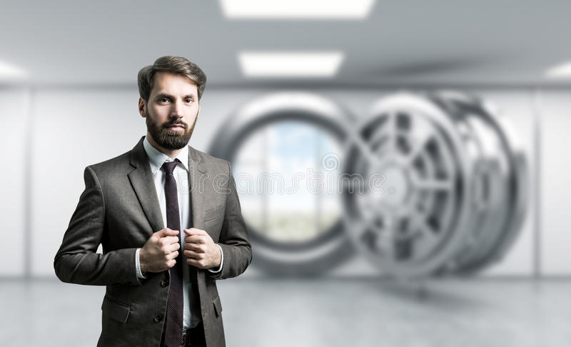 Businessman bank vault. Businessman with bank vault in the background stock photo