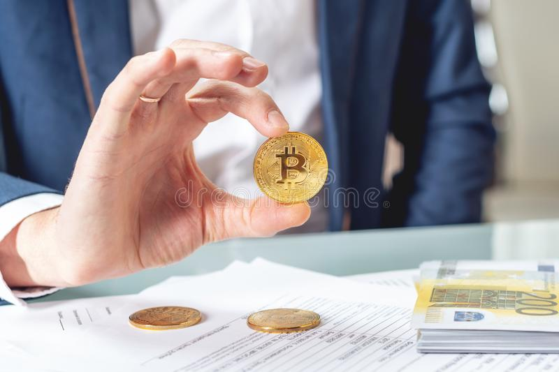 Businessman banker sitting at table with papers holding a coin bitcoin. Exchange and sale of cryptocurrency for Euro stock photos