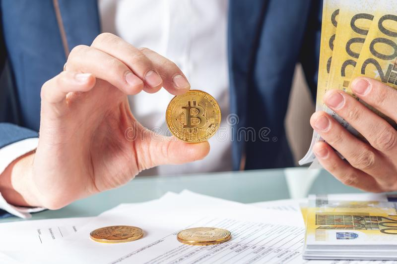 Businessman banker sitting at table with papers holding a coin bitcoin. Exchange and sale of cryptocurrency for Euro royalty free stock photography